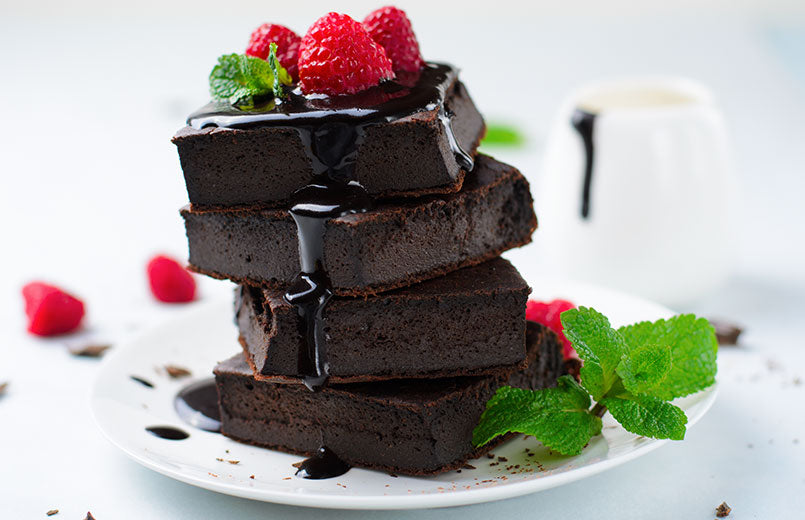 brownie-with-chocolate-sauce-and-raspberry-on-top-on-white-plate