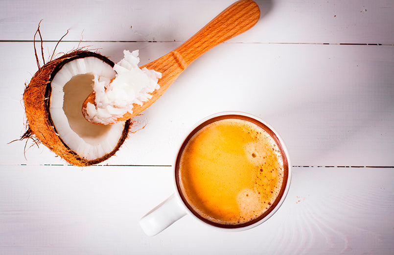 bulletproof-coffee-with-one-half-of-coconut-on-a-wooden-background