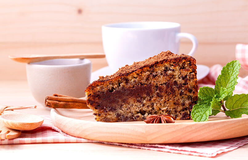 cake-slice-on-a-wooden-plate-with-cups-of-coffee-in-the-background