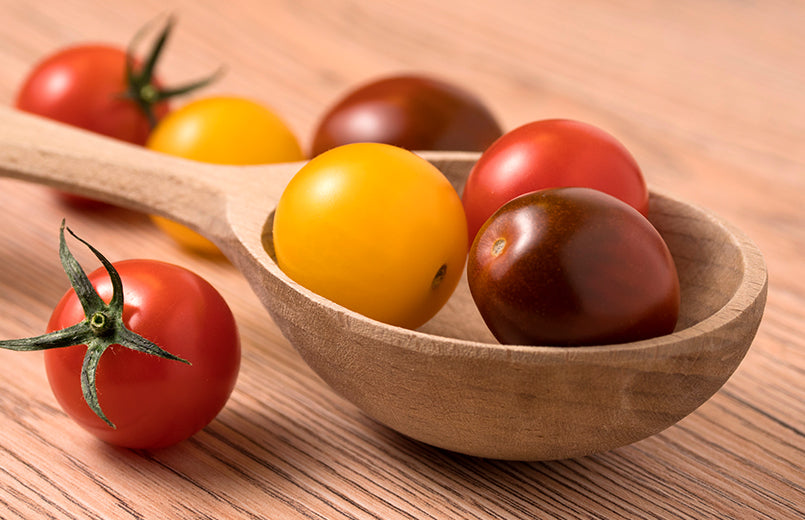 cherry-tomatoes-in-a-variety-of-colors-in-wooden-spoon-on-a-wooden-table