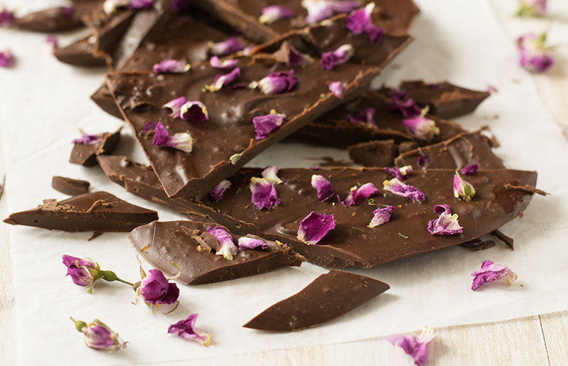 chocolate-bar-with-rose-petals-on-paper-light-background
