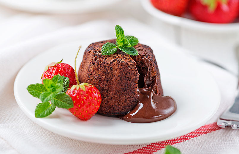 chocolate-fondant-lava-cake-with-strawberries-and-mint-leaves-on-a-white-plate-close-view