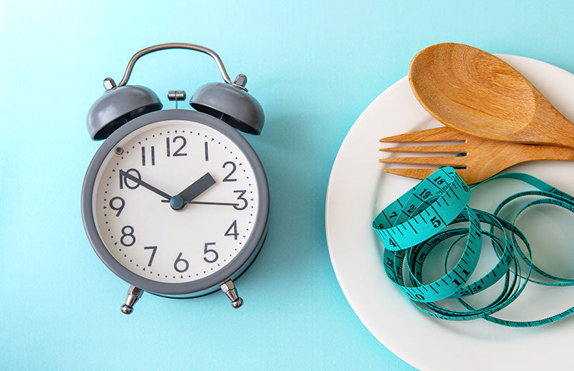 clock-near-empty-white-plate-with-measuring-tape-and-wooden-spoon-and-fork-on-blue background-intermittent-fasting-concept