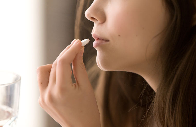 close-up-image-of-woman-putting-white-round-pill-in-mouth