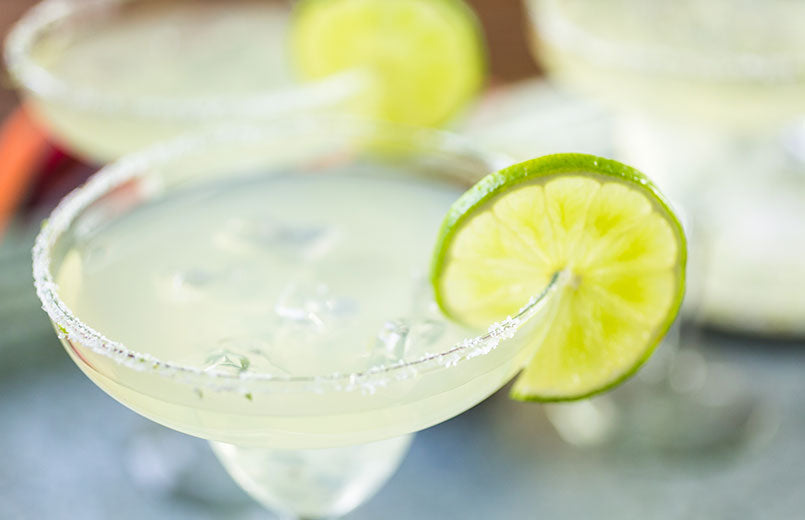 close-up-of-fresh-lime-margarita-cocktail-with-sliced-lime-in-drink-and-wooden-cutting-board-filled-with-limes-and-knife