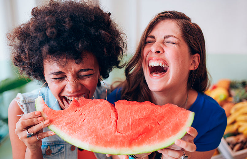 close-up-of-two-female-friends-eating-a-watermelon-slice-and-laughing-together