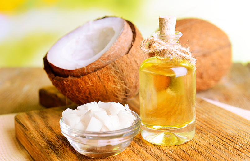 coconut-oil-in-a-bowl-and-mct-oil-in-a-bottle-on-a-wooden-board-with-coconuts-in-the-background