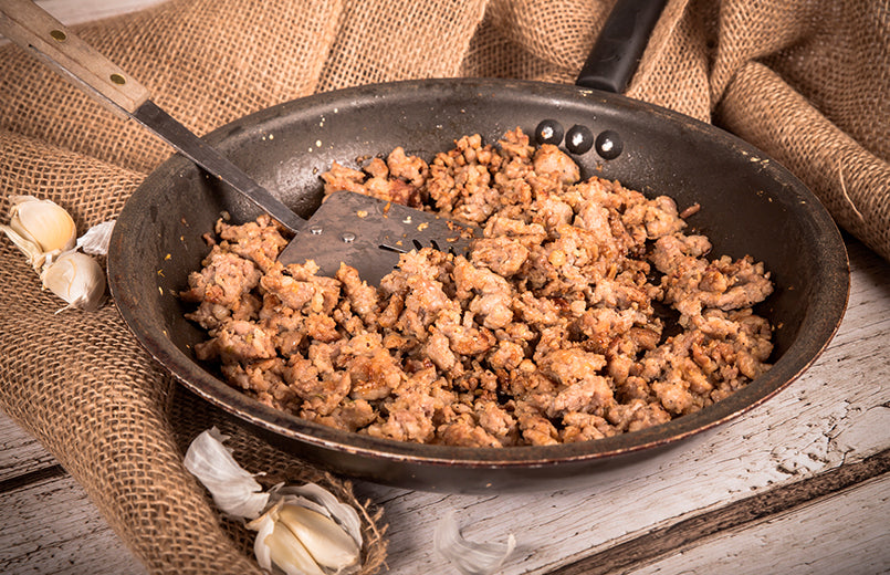 cooking-ground-sausage-meat-in-frying-pan-with-garlic-and-burlap-background