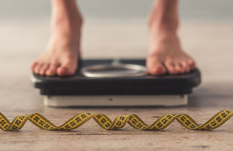 cropped-image-of-woman-feet-standing-on-weigh-scales-on-gray-background-with-a-tape-measure-in-the-foreground