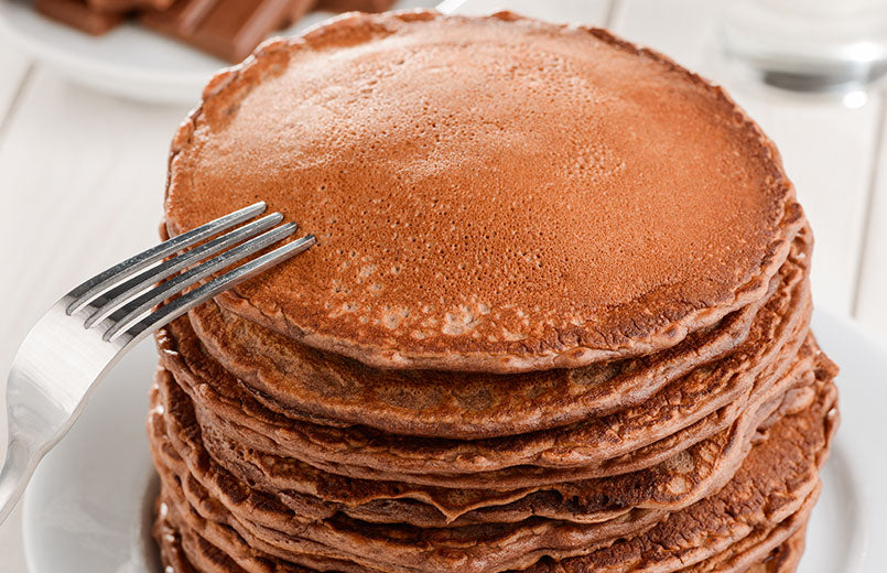 fork-on-a-pile-of-chocolate-pancakes-on-a-white-wooden-table
