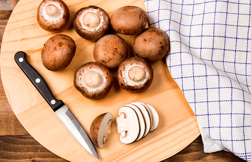 fresh-and-sliced-chestnut-mushroom-with-small-knife-on-a-wooden-board