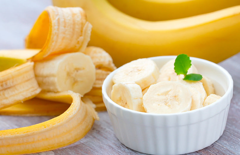 fresh-banana-slices-in-a-white-bowl-on-a-table-with-bananas-in-the-background
