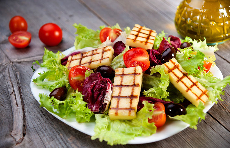fresh-mixed-salad-with-grilled-cheese-on-grey-wooden-table-with-tomatoes-and-olive-oil-bottle-in-the-background