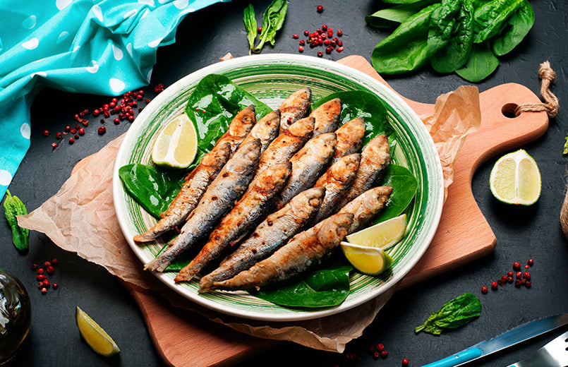 fried-sardines-on-spinach-leaves-on-a-green-plate-on-a-dark-background