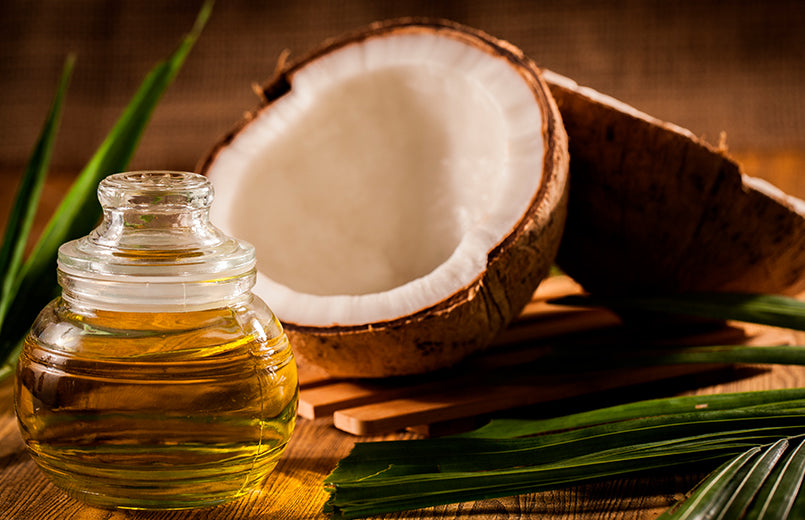 glass-bottle-of-coconut-oil-on-a-table-with-coconut-on-the-background