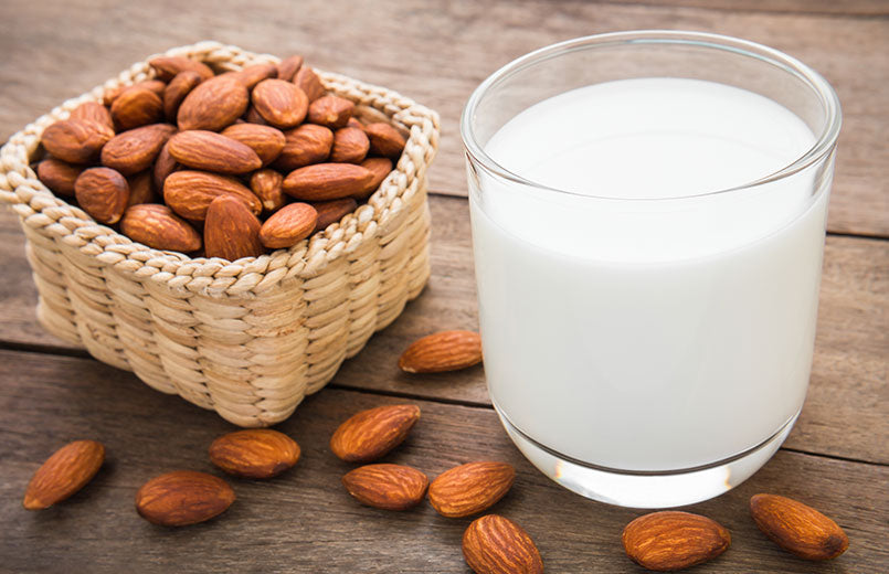 glass-of-almond-milk-and-almonds-on-a-wooden-table