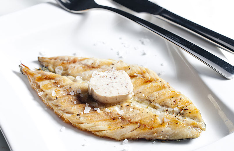 grilled-mackerel-filet-with-butter-on-top-served-on-white-plate-with-knife-and-fork
