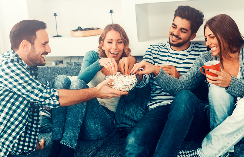 group-of-friends-having-fun-at-home-eating-popcorn-and-enjoying-together