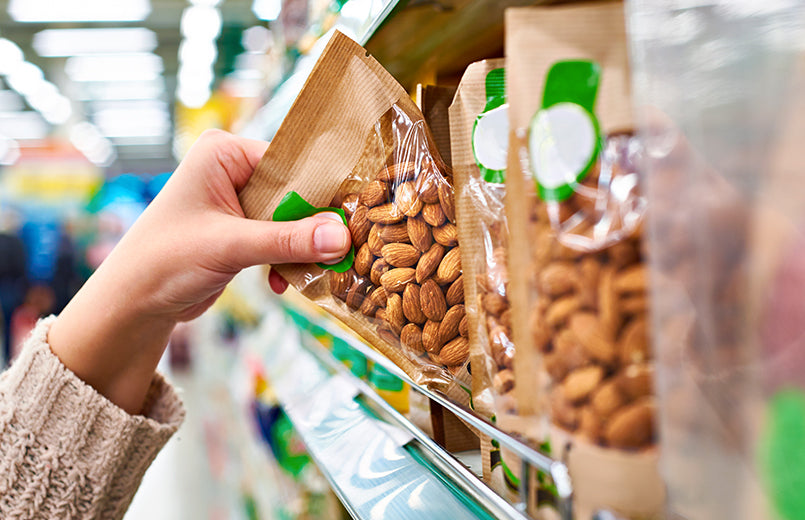 hand-of-the-buyer-with-the-packaging-of-almond-nuts-in-the-store