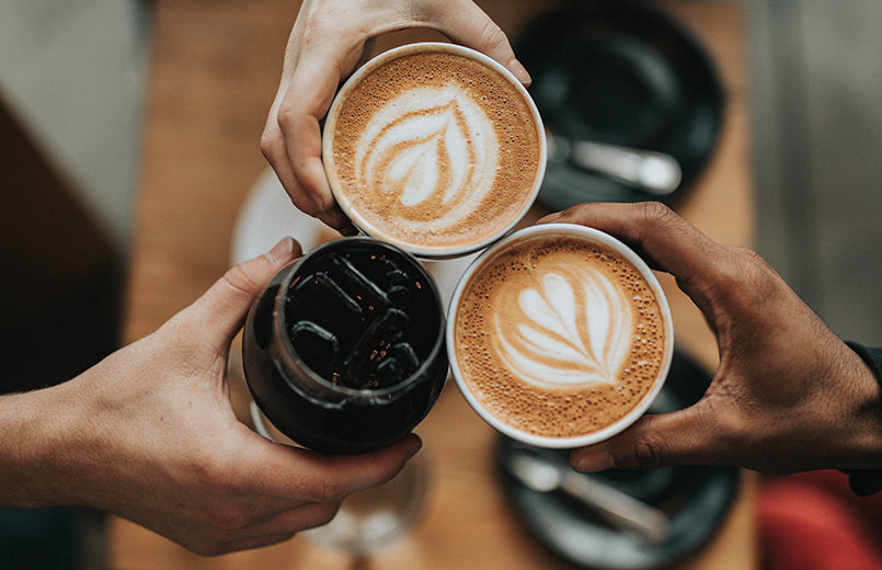 hands-holding-three-coffee-beverages