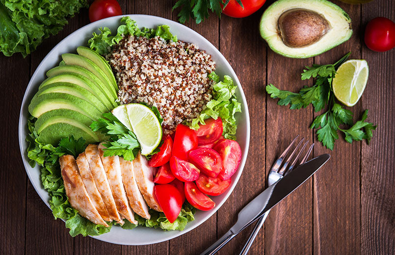 healthy-salad-bowl-with-quinoa-tomatoes-chicken-avocado-lime-and-mixed-greens-lettuce-parsley-on-wooden-background-top-view.jpg