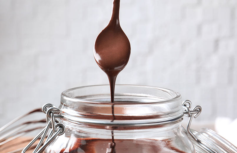 jar-with-delicious-chocolate-sauce-and-spoon-on-light-background