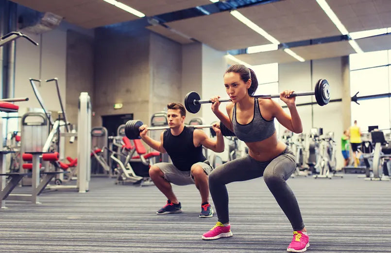 man-and-woman-doing-barbell-exercices-in-a-gym
