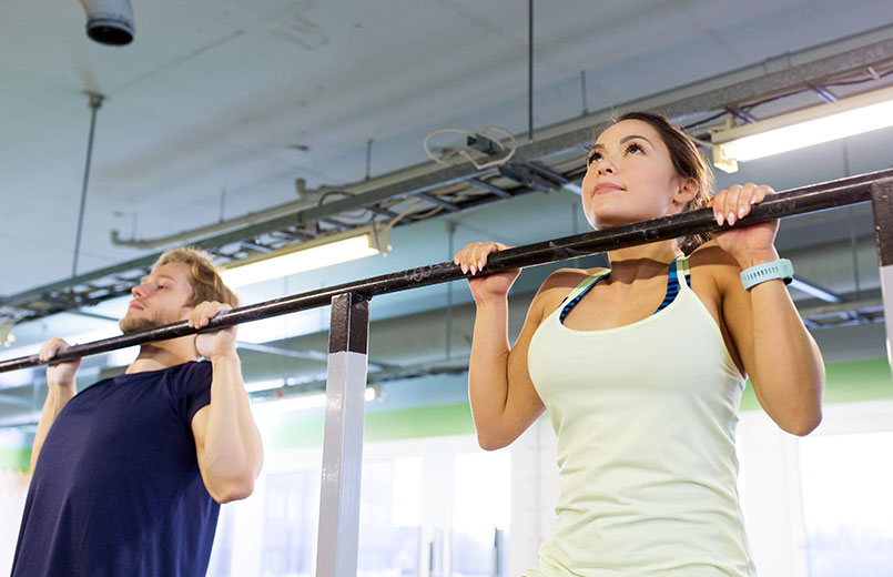 man-and-woman-doing-pull-ups-at-horizontal-bar-in-gym