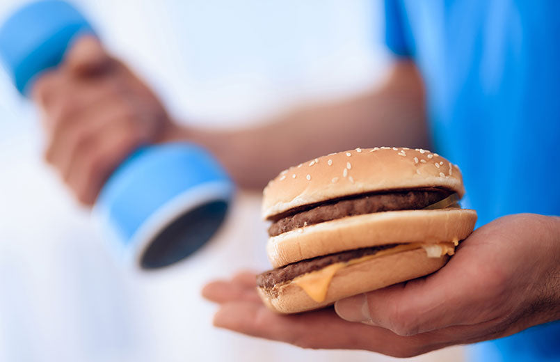 man-in-a-gym-holds-a-hamburger-in-one-hand-in-another-dumbbell