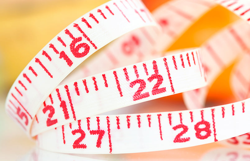 measuring-tape-on-orange-background-fat-loss-concept