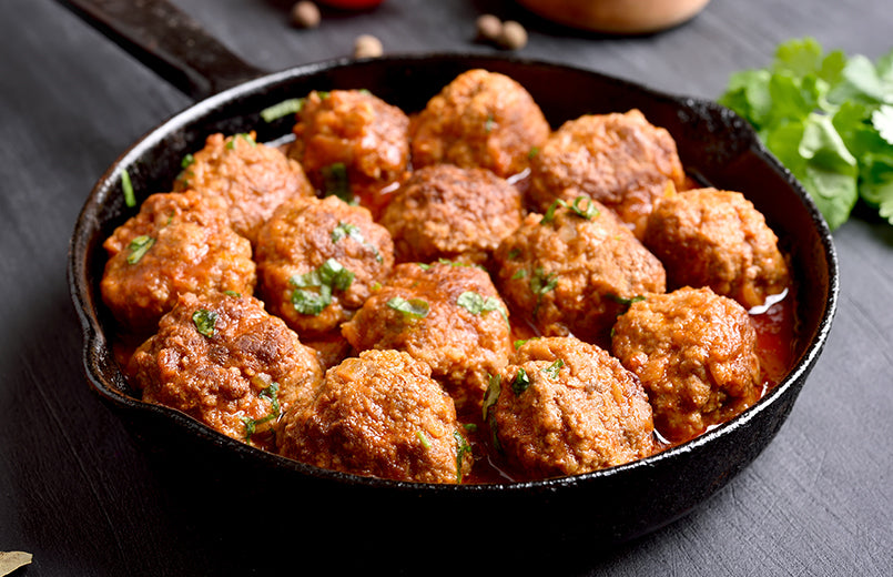 meatballs-in-a-pan-with-sauce-on-dark-wood-table