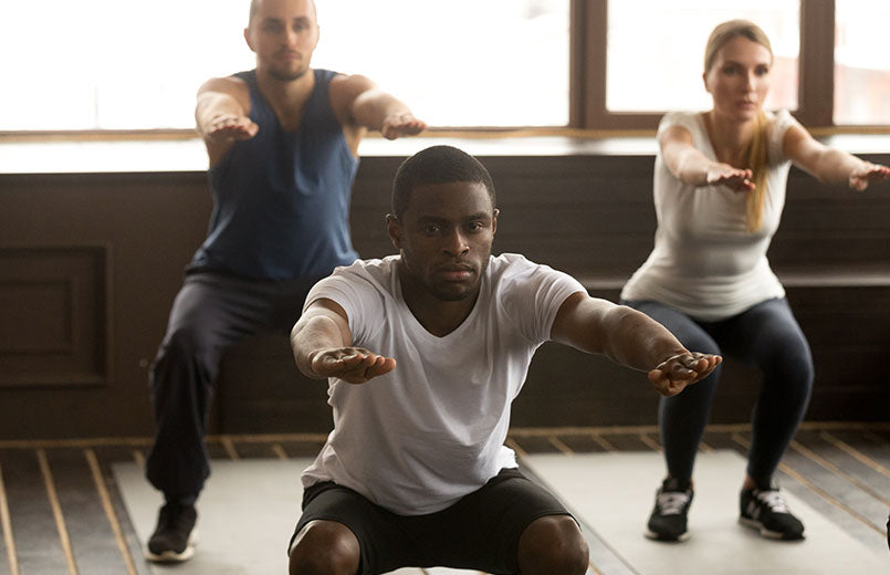 men-and-woman-doing-squat-exercise-at-group-fitness-training