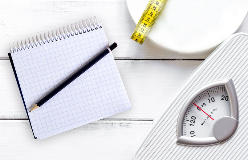 notebook-scale-and-measuring-tape-on-a-white-plate-with-white-wooden-background