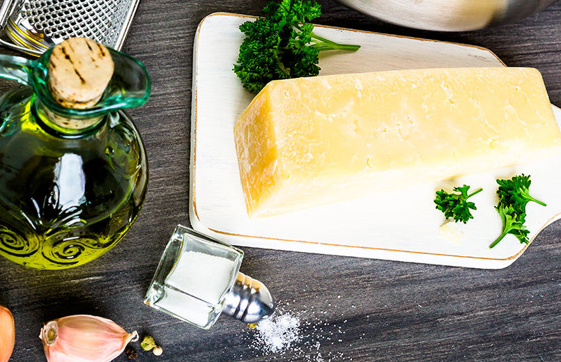 olive-oil-parmesan-cheese-on-cutting-board-and-garlic-on-dark-wood-table
