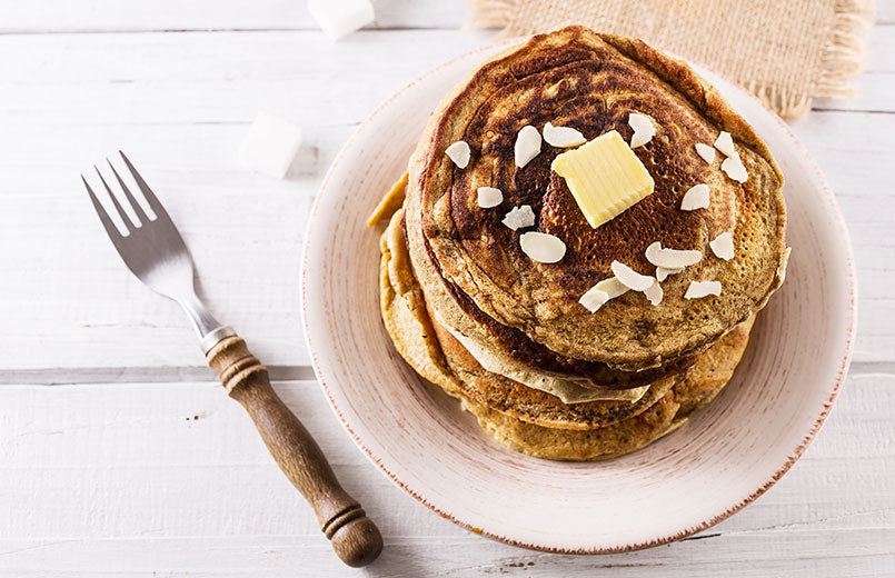 pancakes-with-butter-over-white-wooden-background-close-up