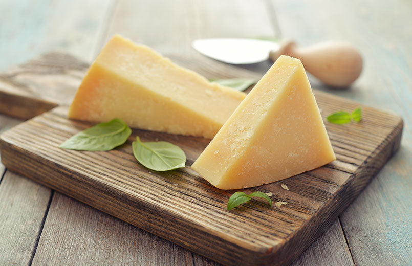 parmesan-cheese-on-cutting-board-with-basil-and-knife-on-wooden-background