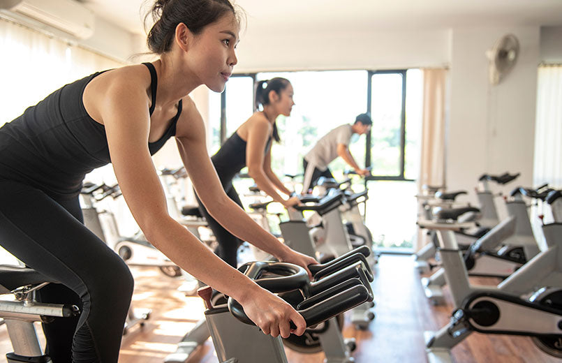people-exercising-on-stationary-bikes-at-a-gym
