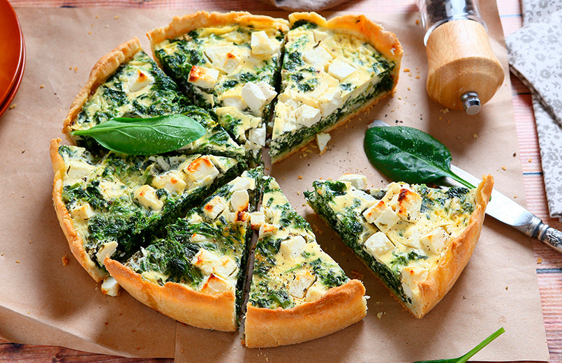 pie-with-spinach-and-cheese-sliced-on-a-baking-parchment
