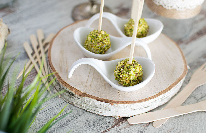 pistachio-cheese-balls-with-skewers-served-on-white-spoons
