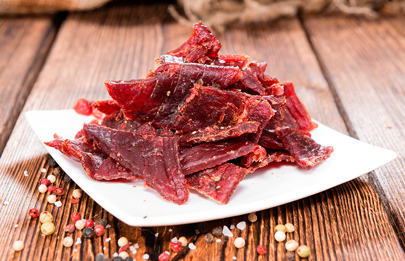 portion-of-Beef-Jerky-on-white-plate-with-vintage-wooden-background