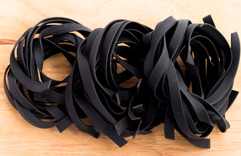 raw-black-fettuccine-on-wooden-background