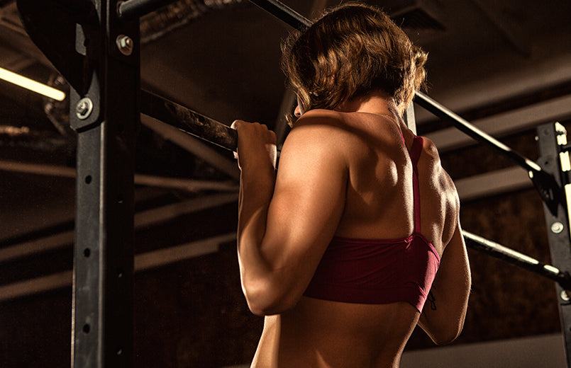 rearview-shot-of-an-athletic-woman-with-muscular-fit-and-toned-body-doing-pull-ups-at-the-gym