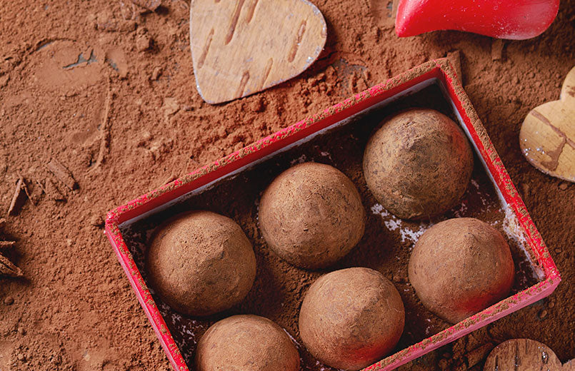 red-gift-box-with-chocolate-truffles-covered-in-cocoa-powder-on-cocoa-powder-background-with-heart-decorations
