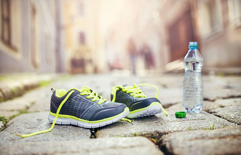 running-shoes-and-bottle-of-water-on-pavement-close-view