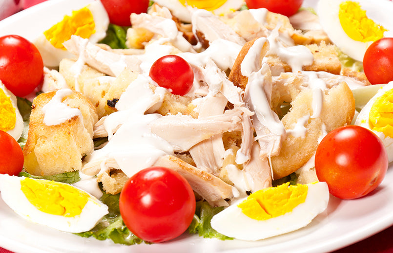 salad-with-hard-boiled-eggs-chicken-lettuce-and-tomatoes-on-a-white-plate-
