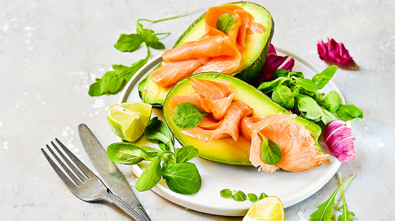 salmon-and-avocado-salad-with-arugula-on-a-white-plate