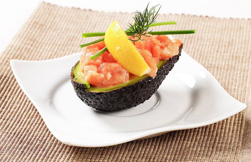 salmon-served-on-avocado-half-on-a-white-plate-placed-on-a-light-brown-towel