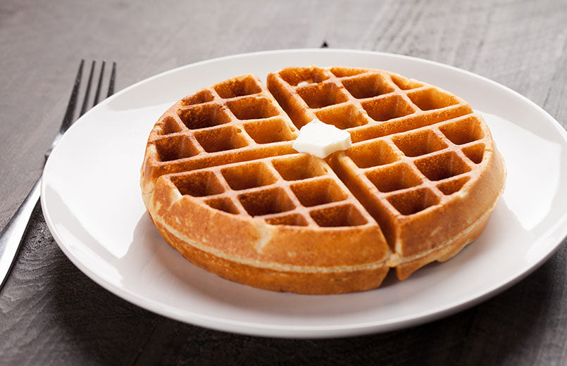 simple-belgian-waffle-on-a-white-plate-with-fork-on-wooden-background