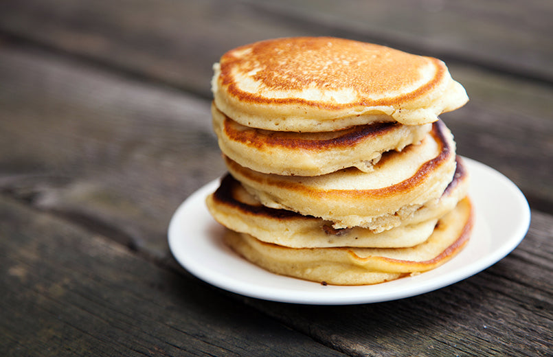 stack-of-pancakes-on-white-plate-with-wooden-background