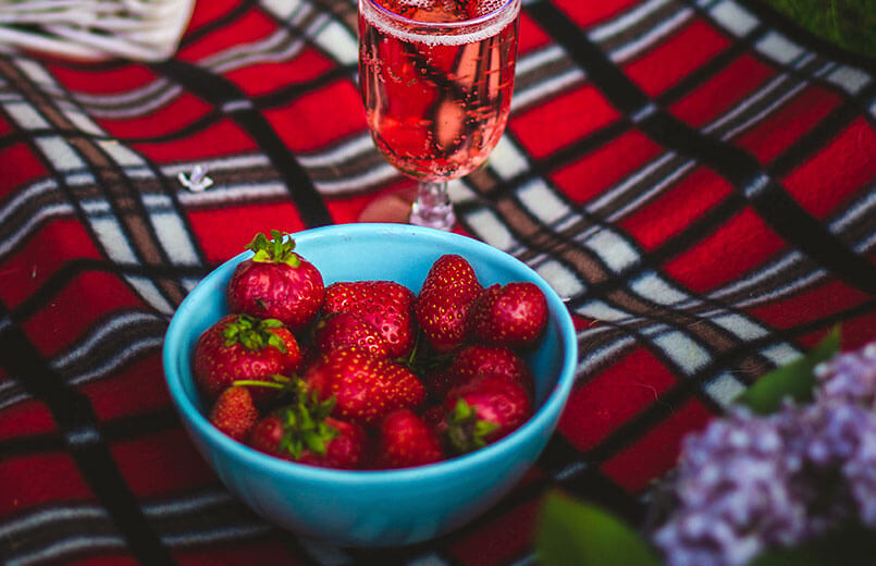 strawberries-in-a-blue-bowl-on-a-picnic-blanket-with-a-glass-of-strawbery-sparkling-water-in-the-background